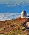 Observatoriet med den sølvskinnende kuppel på en bjergtop over skyerne i baggrunden, med en servicebygning ved siden af.